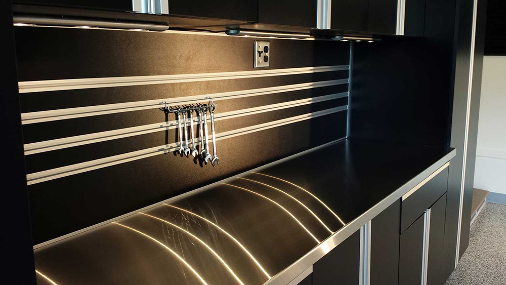 garage-black-cabinets-lighting-steel-countertop